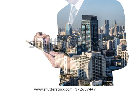 Double exposure of business man hand hold and touch screen tablet, day city as communication concept. - stock photo