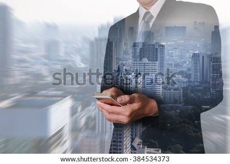 Double exposure of business man hand touch screen smart phone, mobile and city in a foggy morning as communication and technology concept. - stock photo