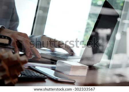 double exposure of business man hand working on laptop computer on wooden desk as concept  - stock photo