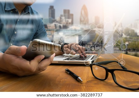 double exposure of business man hand working on laptop computer on wooden desk with social media network diagram - stock photo