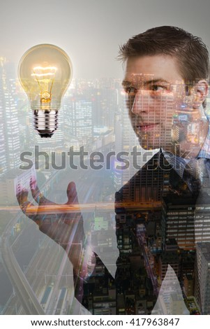 Double exposure of Business man holding light bulb with cityscape - stock photo