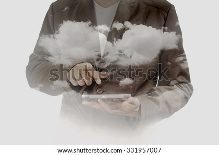Double exposure of Business Man using Mobile Tablet PC with Cloud and Sky as Cloud Computing or Network concept. - stock photo