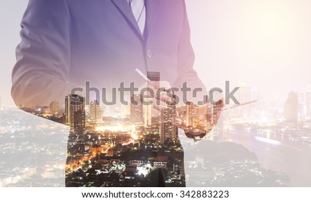 Double exposure of Business man working with a digital tablet with cityscape blurred building background, Business Trading concept - stock photo
