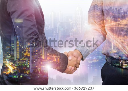 Double exposure of businessman handshake and city. - stock photo