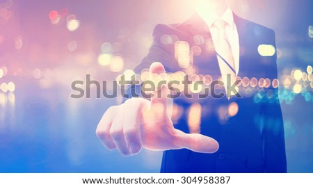 Double exposure of businessman pointing at something on blurred city background - stock photo