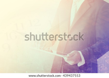 Double exposure of businessman using the tablet with cityscape,finance amd stock market  on blurred building background, Business Trading concept - stock photo