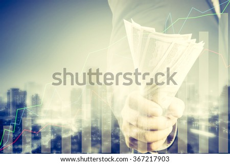 Double exposure of Businessman with money in hand and financial graph on cityscape blurred building background, success and profitable business concepts,Business Trading concept - stock photo