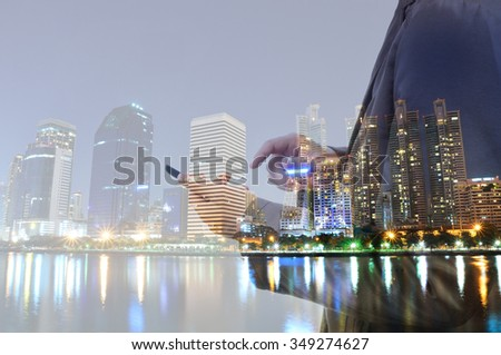 Double exposure of city and business man using digital smartphone device as Business development concept. - stock photo