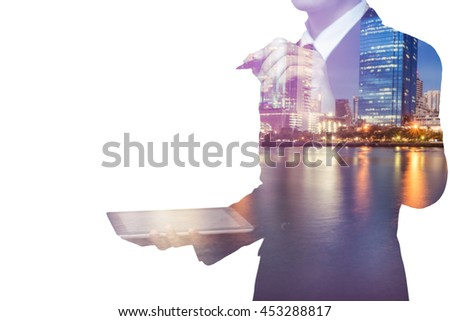 Double exposure of city and business man using tablet - stock photo