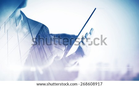 Double exposure of city and hands using tablet - stock photo