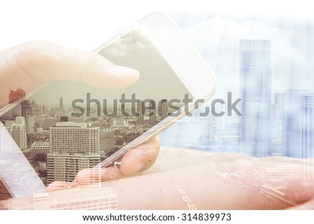Double exposure of hand with mobile phone - stock photo