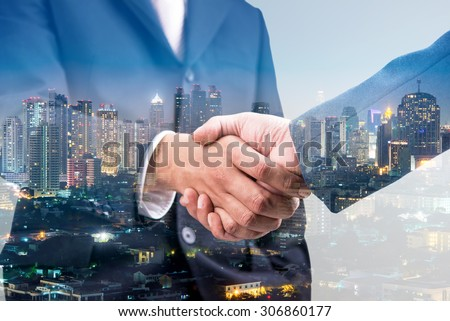 Double exposure of handshake and city  - stock photo