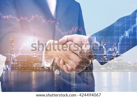 Double exposure of handshake and refinery plant at night with stock graph  - stock photo