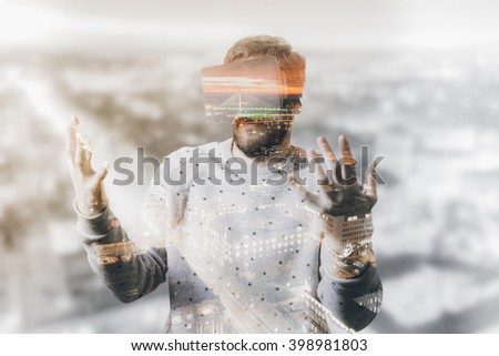 Double exposure of man using VR simulator - stock photo