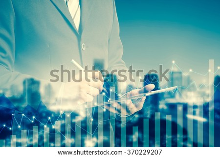 Double exposure of success businessman using digital tablet with city blurred background.Forex graph on the business city centre. A metaphor of international financial consulting.investment concept - stock photo