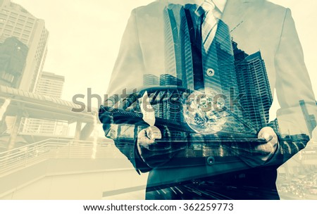 Double exposure of success businessman using digital tablet with city landscape background with the small world (Elements of this image furnished by NASA) - stock photo
