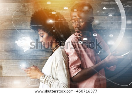 Double exposure of surprised jealous African man looking over his shoulder, watching his stylish African wife texting someone standing back to back, suspicious of her cheating on him. Visual effects - stock photo