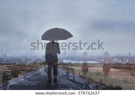 double exposure photo of business man with umbrella and London skyline, panoramic view of the city - stock photo