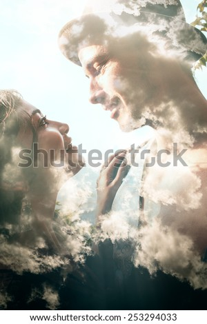 Double exposure portrait of a couple combined with photograph of clouds - stock photo