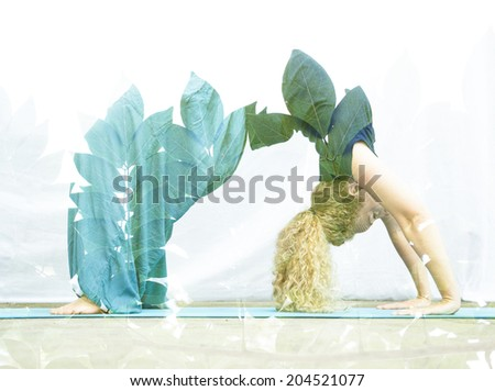 Double exposure portrait of young woman performing back bend combined with photograph of nature - stock photo