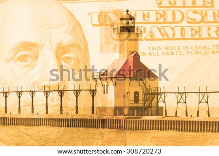Double exposure St. Joseph north pier lighthouse along shoreline of Lake Michigan with hundred dollar bill background - stock photo