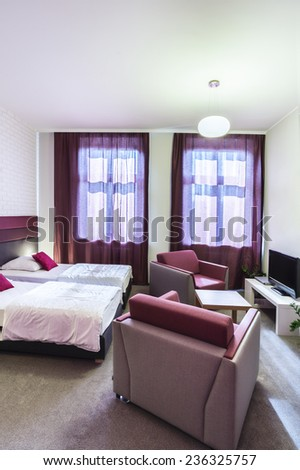 Double hotel room with violet curtains and decorations - stock photo