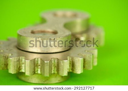 Double joint machinery part of two cylindrical metal cogwheel fragments shot with small depth of field, symbolizing mechanical approach to kinetic movement problems and industrial working terms - stock photo