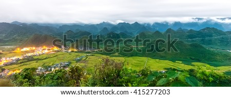 Double Mountain Quan Ba dusk with rolling mountains covered with clouds, beneath the small town with its sparkling lights and green patches of beautiful terraced countryside of Vietnam - stock photo
