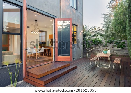 Double open french doors with seating arrangement in contemporary home with wooden terrace, open floor plan at night. - stock photo