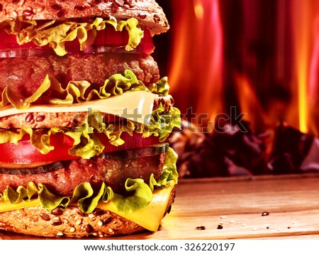 Double patty hamburger on wooden board on background of fire. Food still life. - stock photo