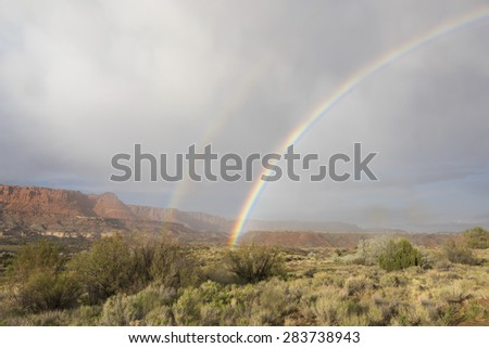 Double Rainbow against a red rock formation - stock photo