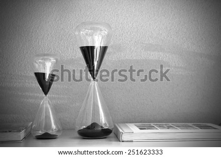 Double sandglasses with magazine in monochrome, conception. - stock photo