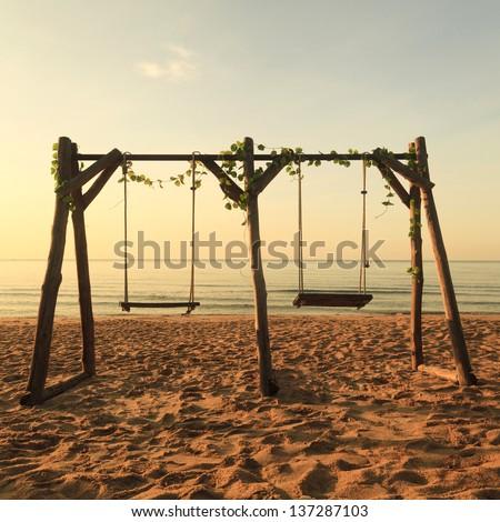 Double swings on the beach - stock photo