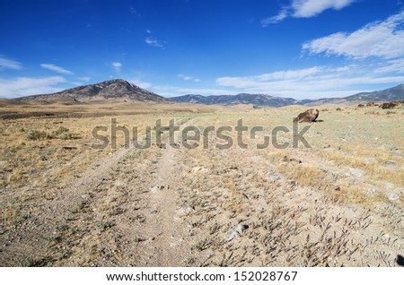 double track gravel road that does not get much traffic heading towards distant Nevada mountains - stock photo