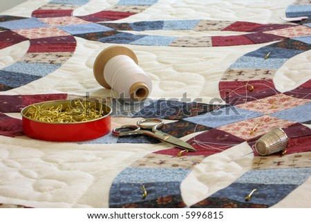 Double wedding ring patterned quilt with quilting tools - stock photo