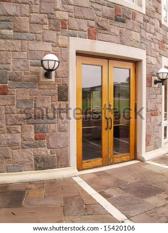double wood doors by a stone building - stock photo