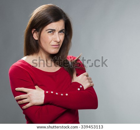 doubt and worry concept - portrait of outraged 30s woman questioning or looking deaf with arms folded for fragility,studio shot - stock photo