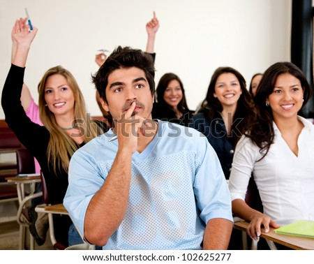 Doubtful man amongst a group of university students in a classroom rising their hands - stock photo