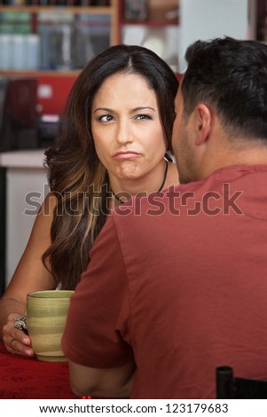 Doubtful woman looking at man sitting in cafe - stock photo