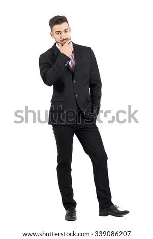 Doubtful young business man with hand on his chin looking at camera. Full body length portrait isolated over white studio background.  - stock photo
