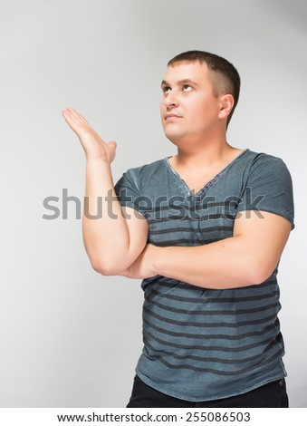 Doubtful young man sitting and gesturing with hands - stock photo