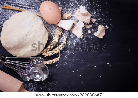 Dough and ingredients for it - eggs, flour, yeast on dark slate background. Selective focus. Place for text. - stock photo