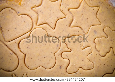 Dough for gingerbread cookie and cookie clipped in different shapes like background. Toned. - stock photo