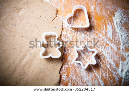 Dough for gingerbread cookie and cookie cutters in different shapes on light wooden cutting board like background. Toned. - stock photo