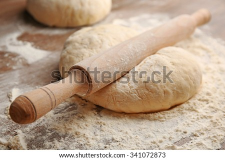 Dough for pizza and rolling-pin on wooden table - stock photo