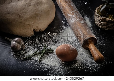 dough on a black board with flour. olive oil, eggs, rolling pin, garlic. Tinted  - stock photo