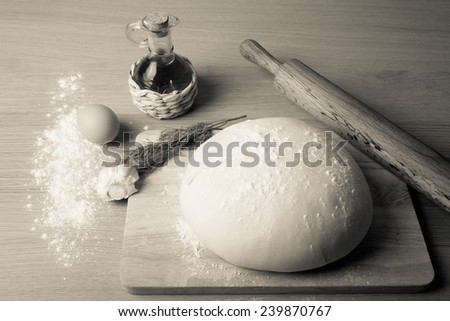 dough on a board with flour. olive oil, eggs, rolling pin, garlic and dill. Tinted. - stock photo