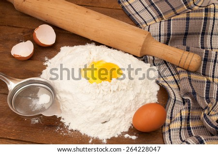 Dough preparation. Baking ingredients: eggs and flour, sieve and rolling pin on wooden background. - stock photo