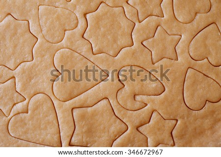 Dough rolled out and various shape cookies cut out with different cutters - stock photo
