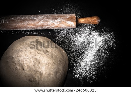 Dough, rolling pin and flour on a black background. Toned. - stock photo